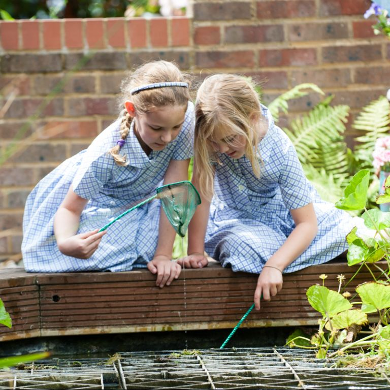 school girls fishing in pond with nets