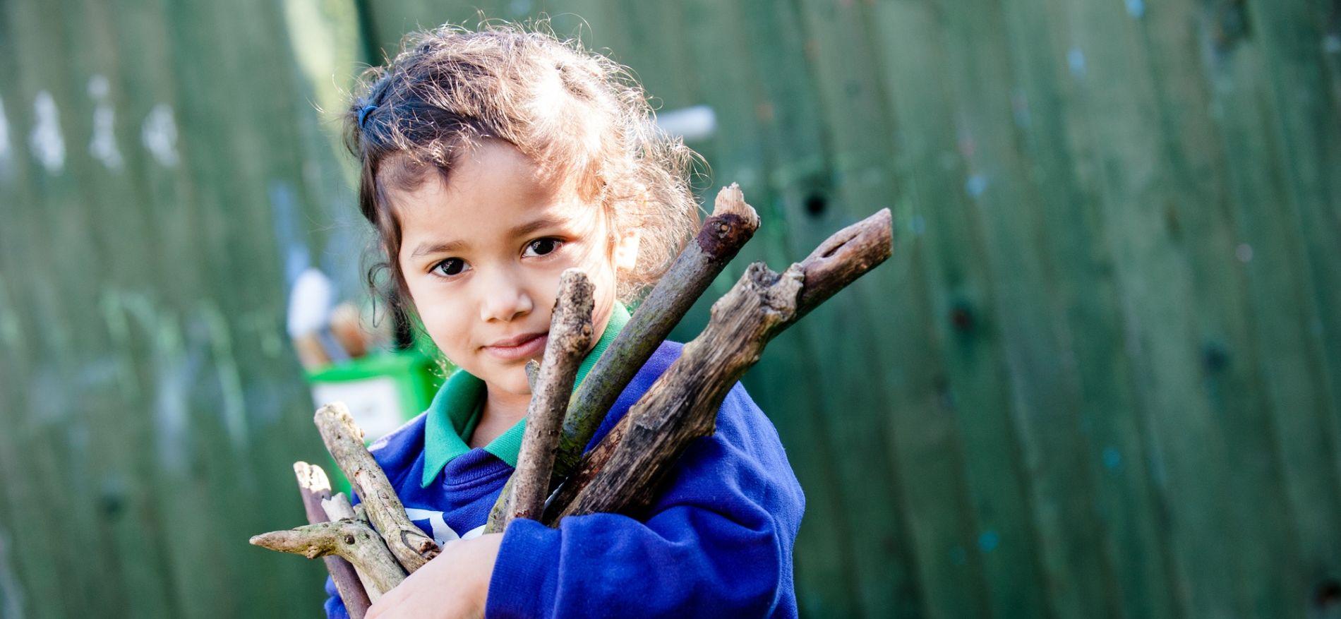 child holding bunch of sticks