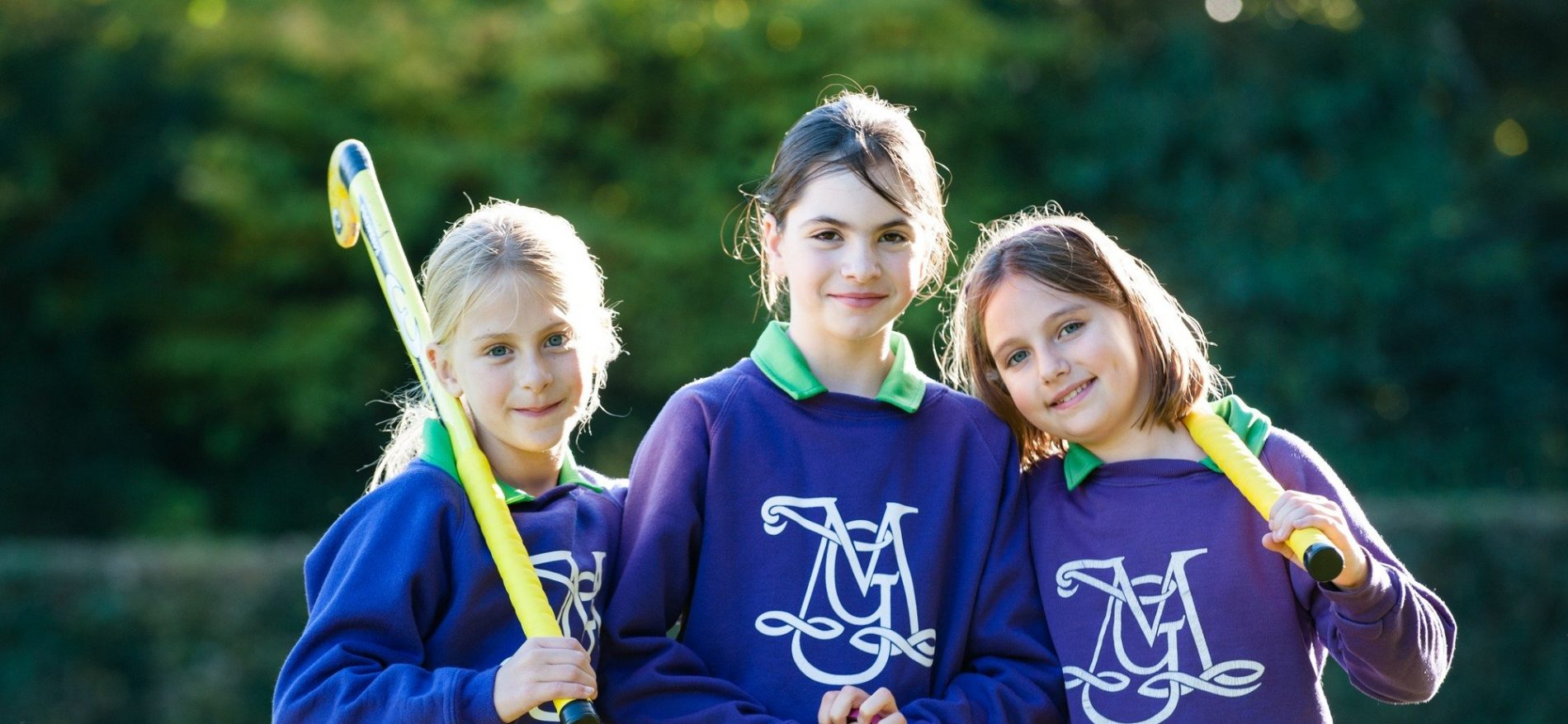 three school girls with hockey sticks