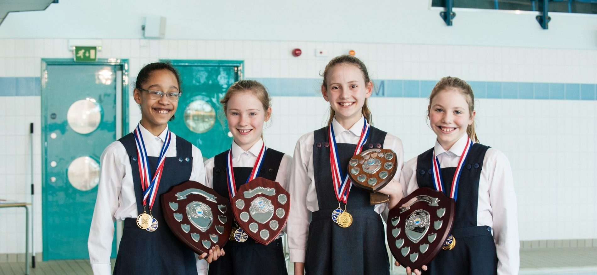 school students holding awards and medals