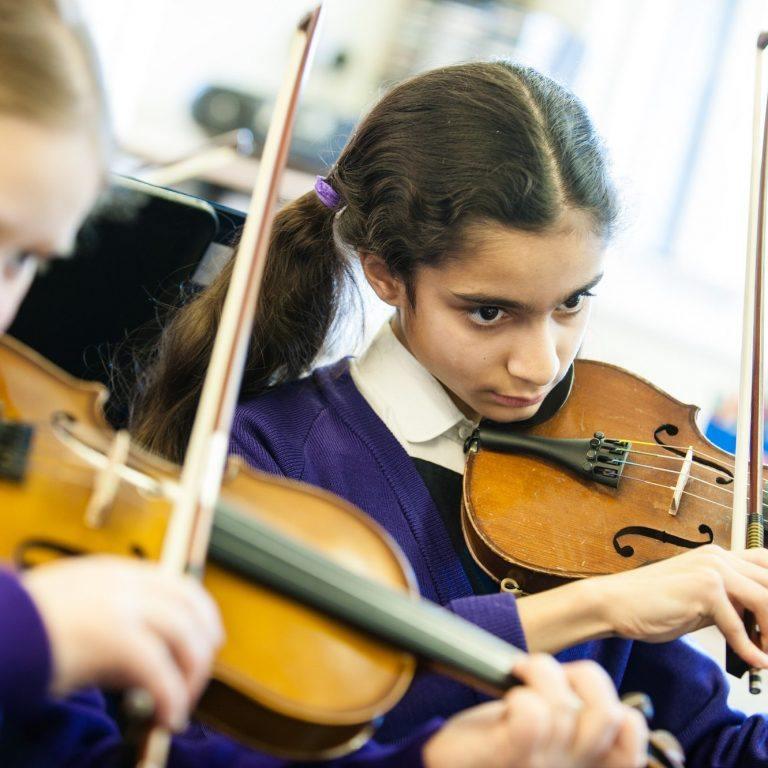 two girls playing violin