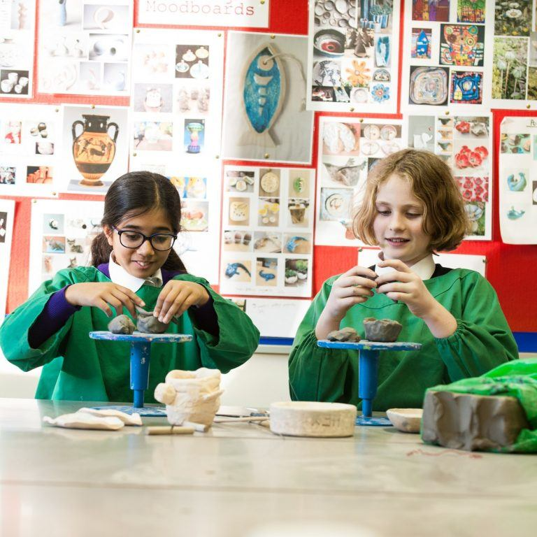 2 girls wearing green aprons over their purple uniform making creations with clay
