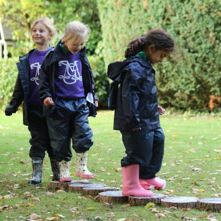 three young girls in waterproof clothing and wellies outside