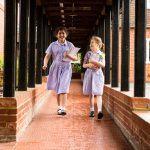 school girls in summer dresses holding books