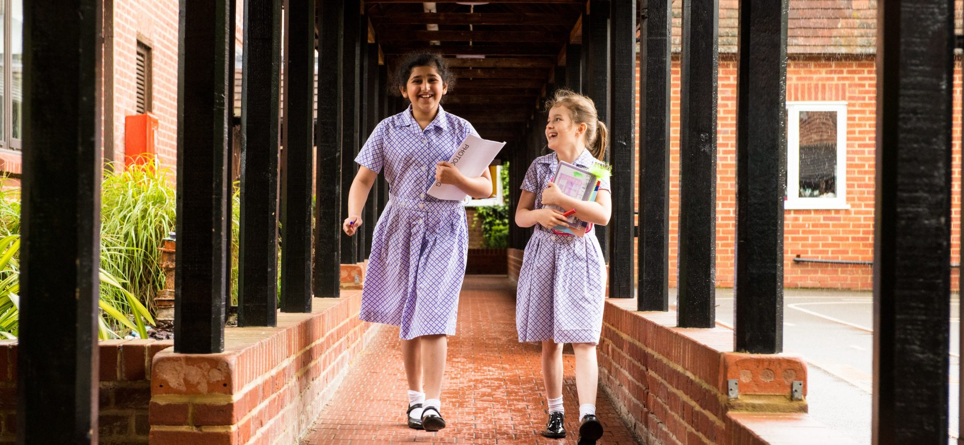 school girls in summer dresses holding books