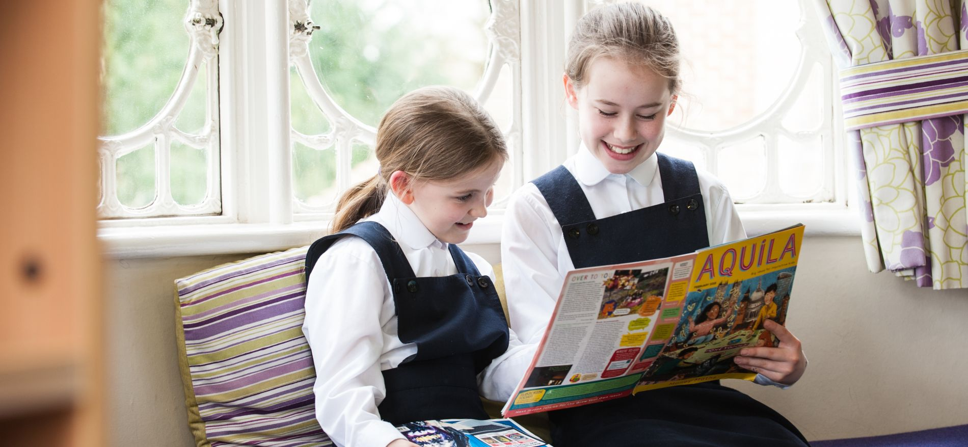 2 young students reading through a magazine titled Aquila