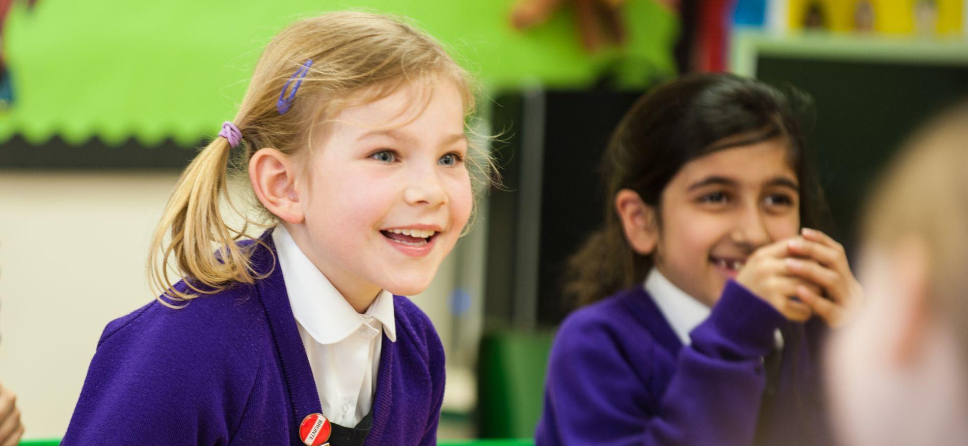 school girls in classroom smiling