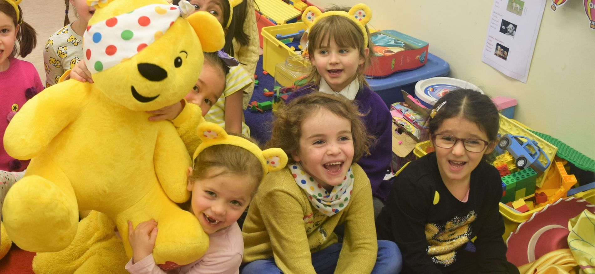 school children with pudsey bear - children in need charity