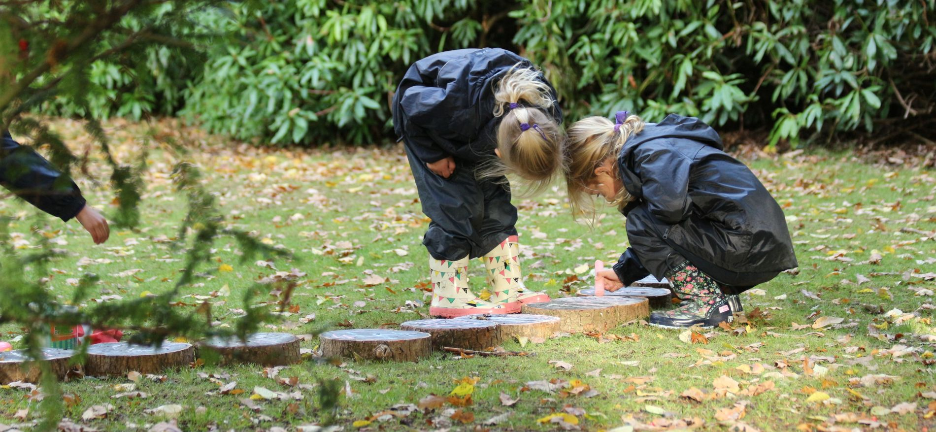 2 schoolgirls using chalk to make creations on tree stumps