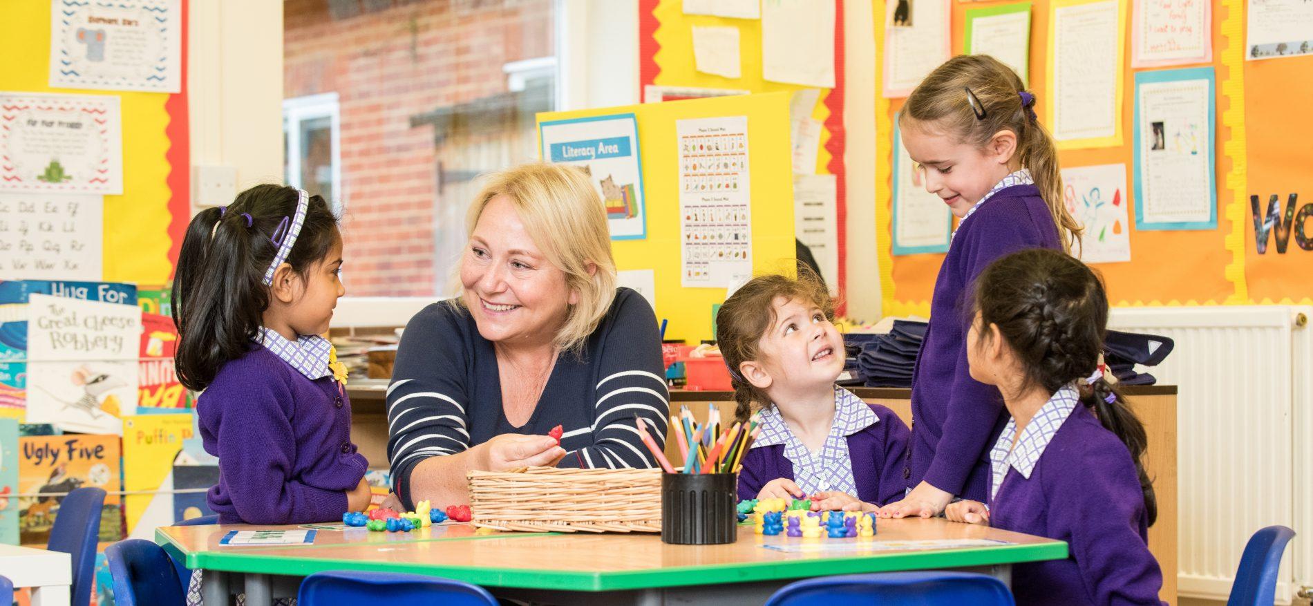 nursery girls with teacher in classroom