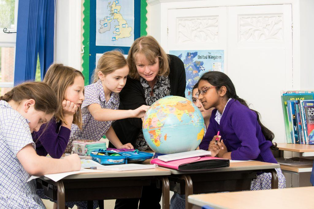 school girls looking at a globe with teacher