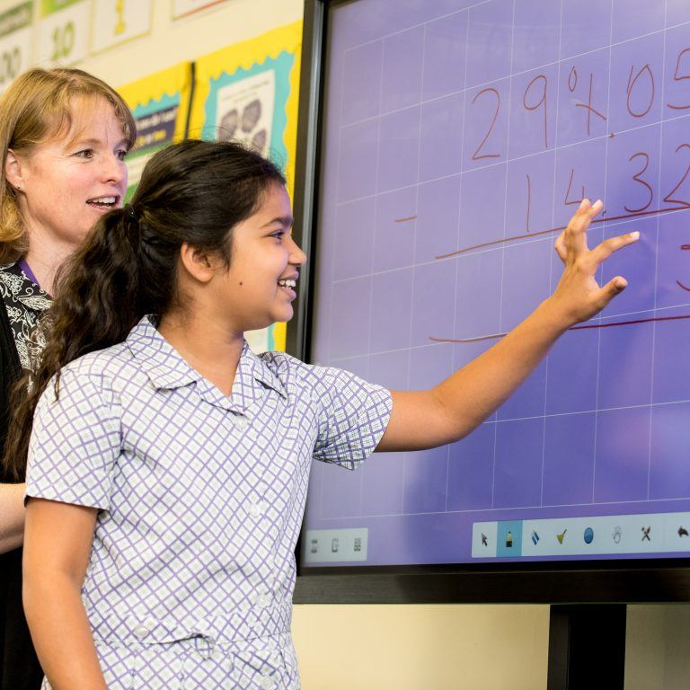 school girl and teacher writing on interactive board
