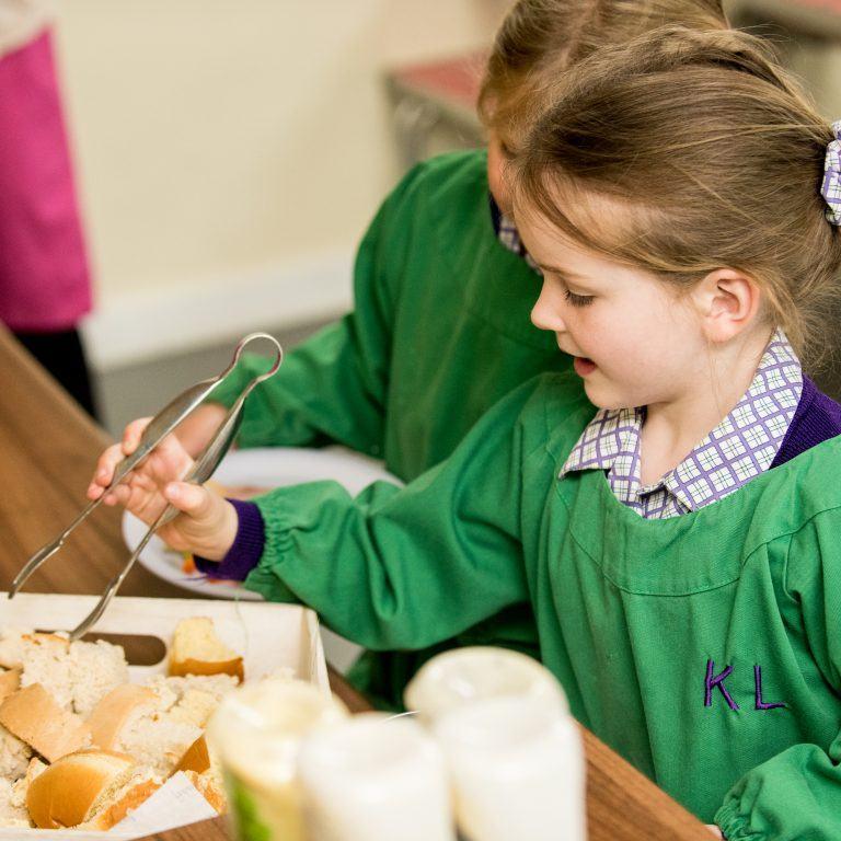 school girl choosing her school dinner bread