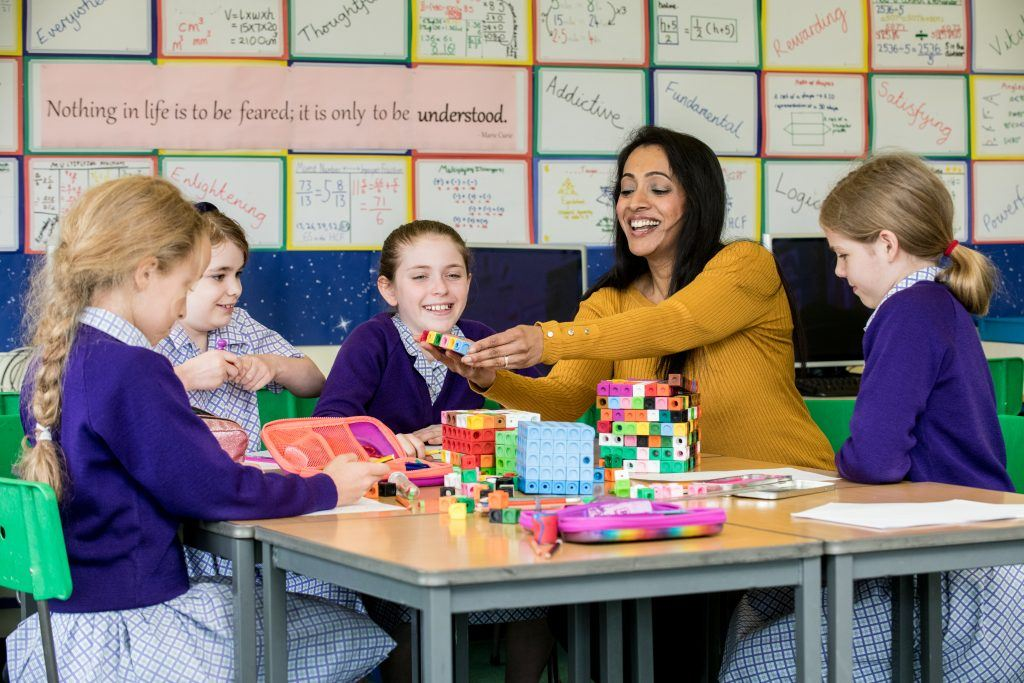 school children learning maths with teacher using cubes