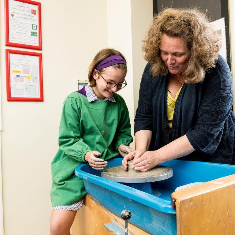 school girl and teacher making clay