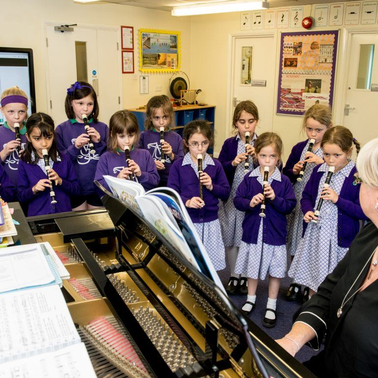 group of young school girls playing recorders