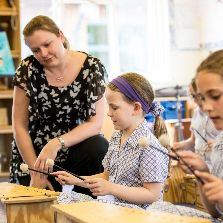 two school girls playing xylophones