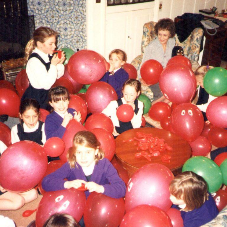 school girls surrounded by balloons