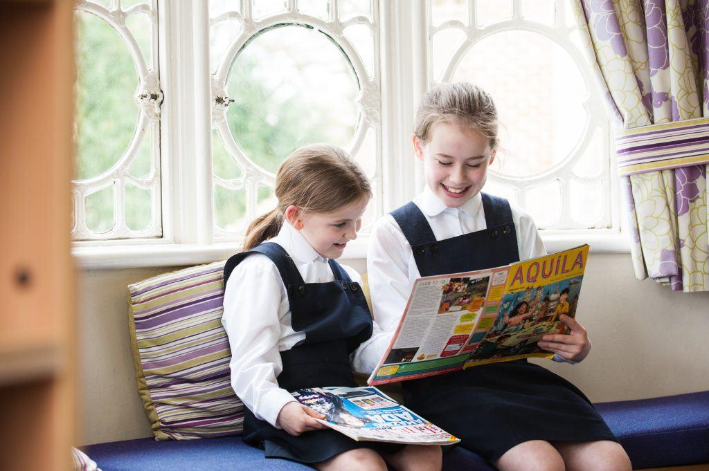 school girls reading by a window
