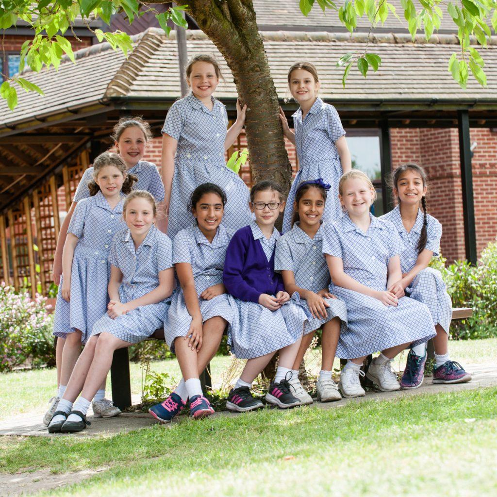 group of school girls sitting around a tree