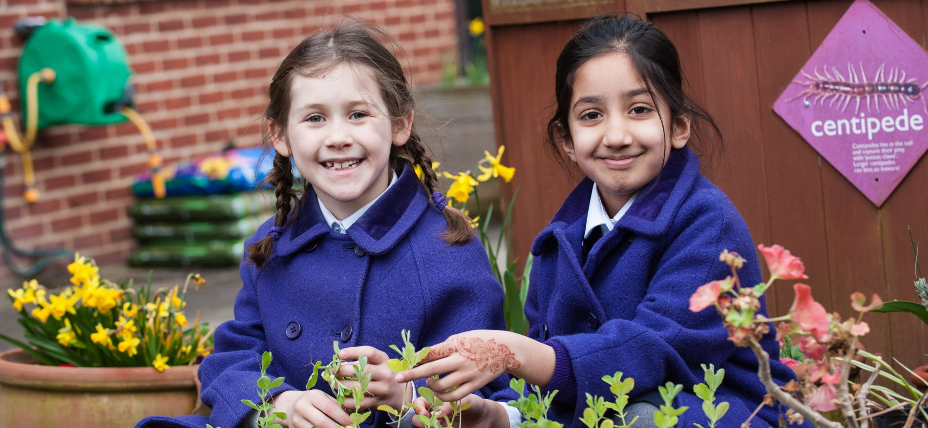 two school girls planting seeds and gardening