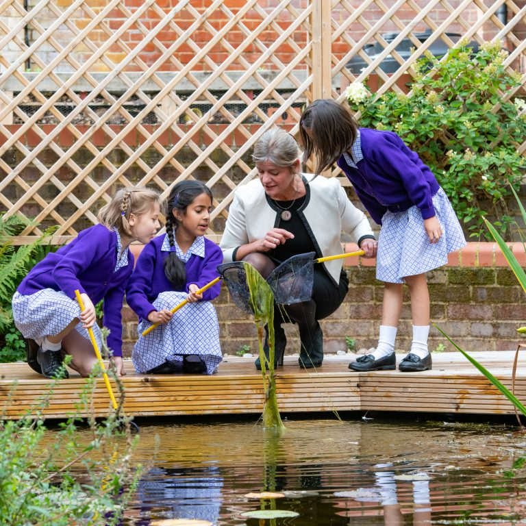 Head teacher looking at pond with school girls