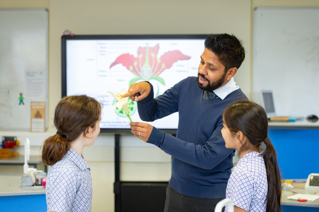 A teacher shows 2 students the different parts of a flower
