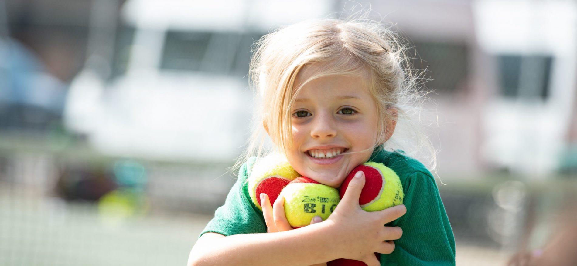 A girl holding a pile of tennis balls