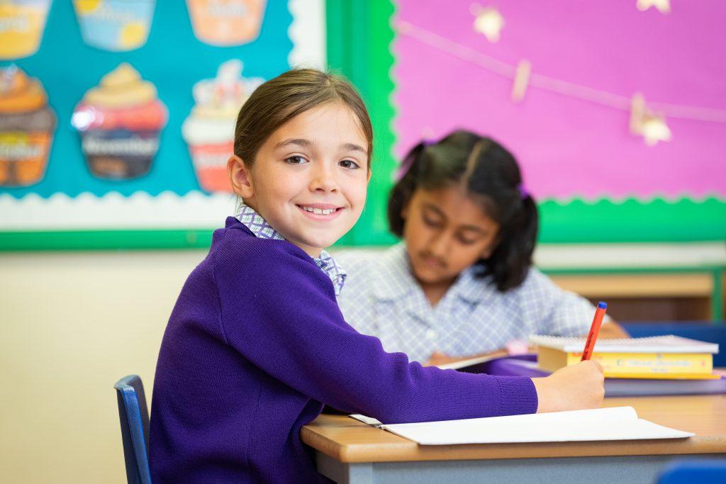 Schoolgirl smiling as they work