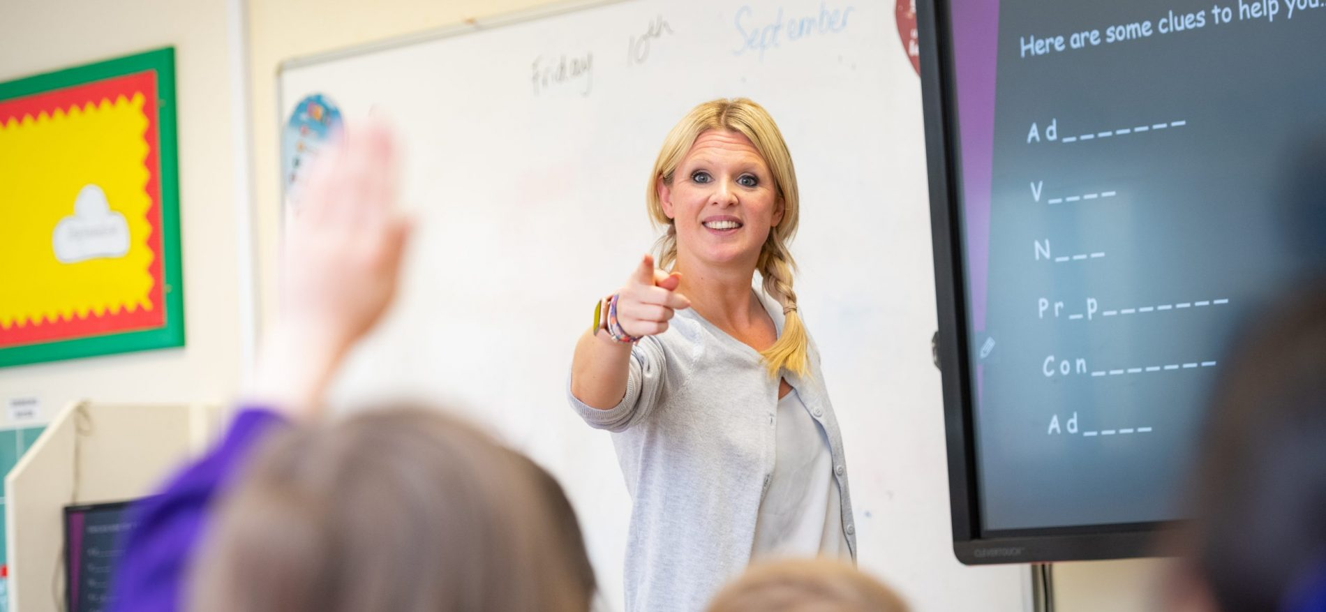 A teacher points to a child who's raised their hand