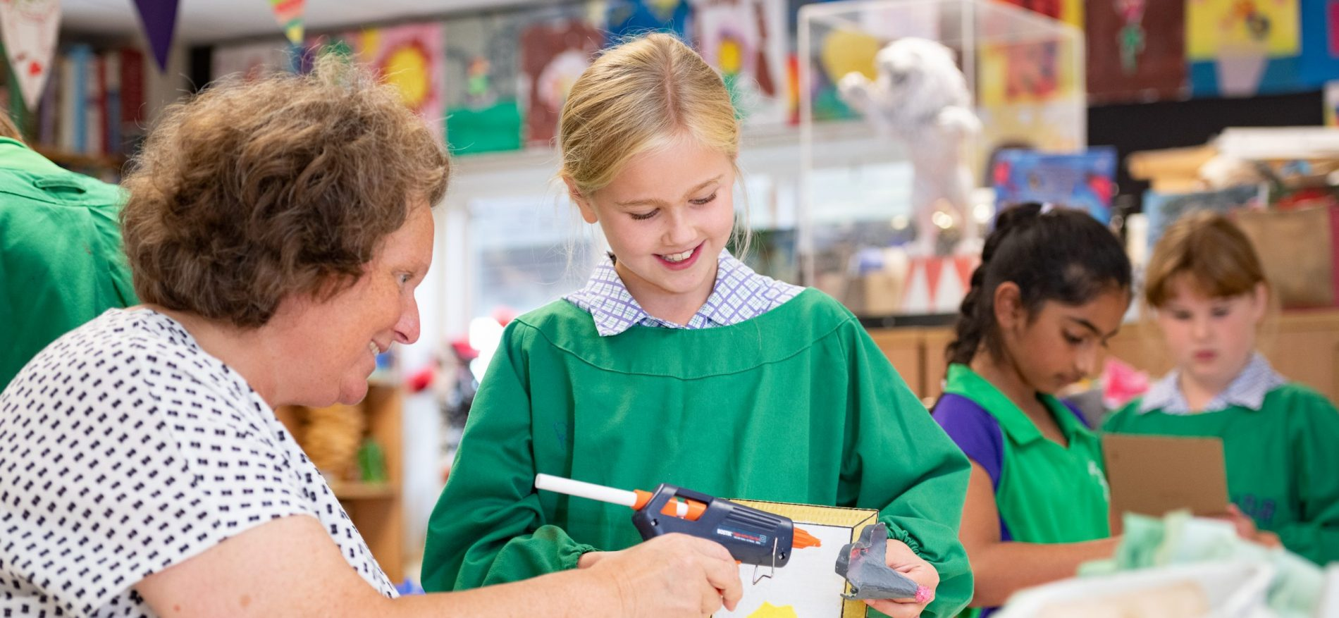 A teacher holds a glue gun against something a child is holding