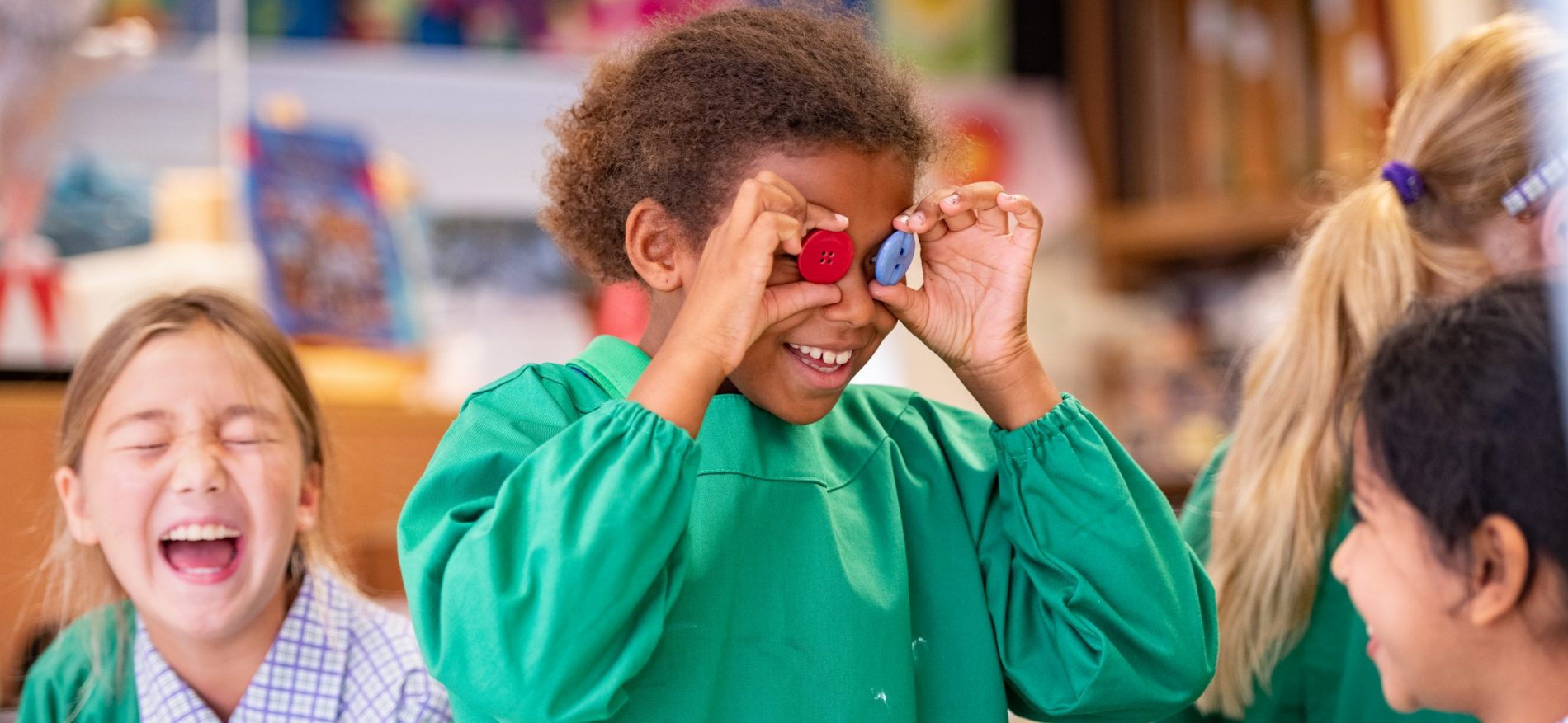 4 school children are in class - one girl has placed buttons over her eyes much to the joy of the other students