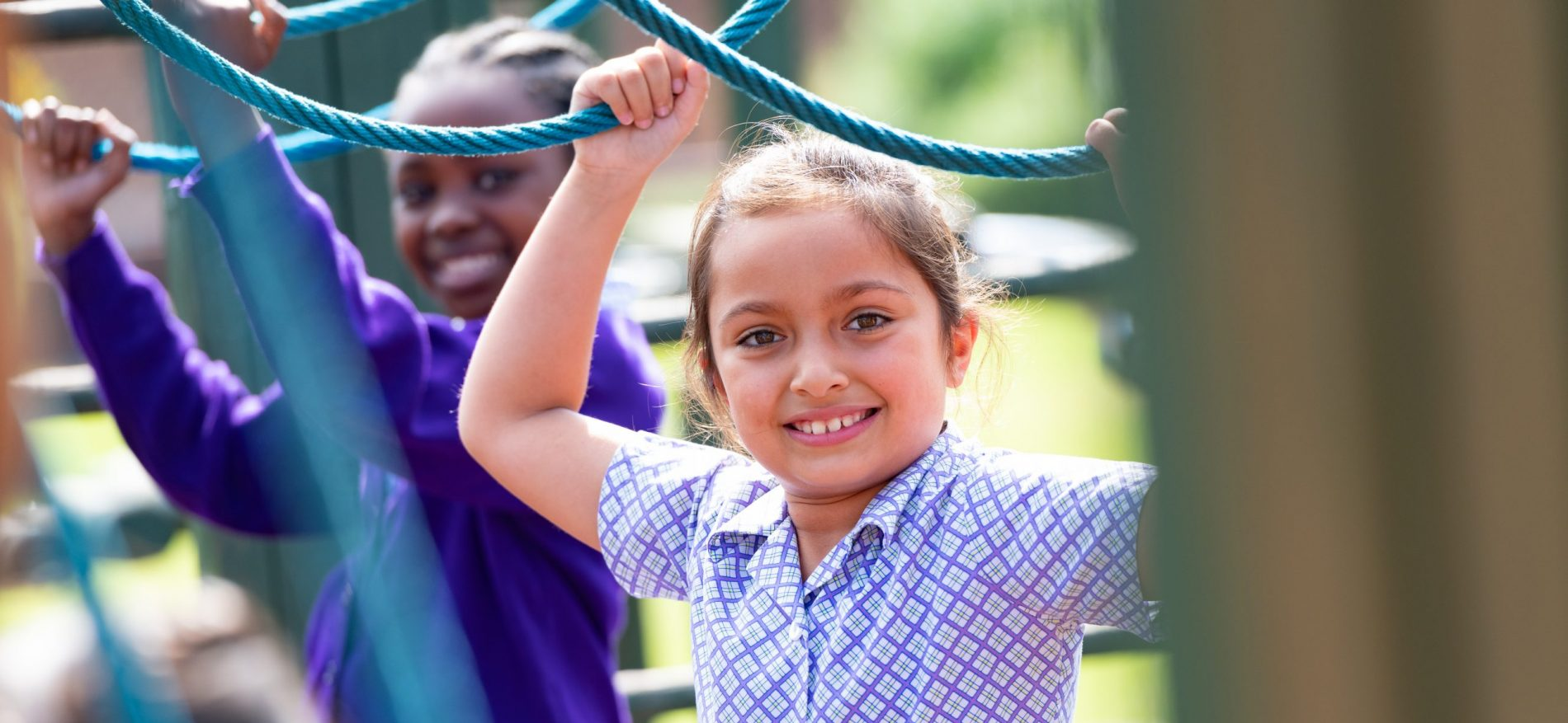 2 girls are holding ropes high at the play park