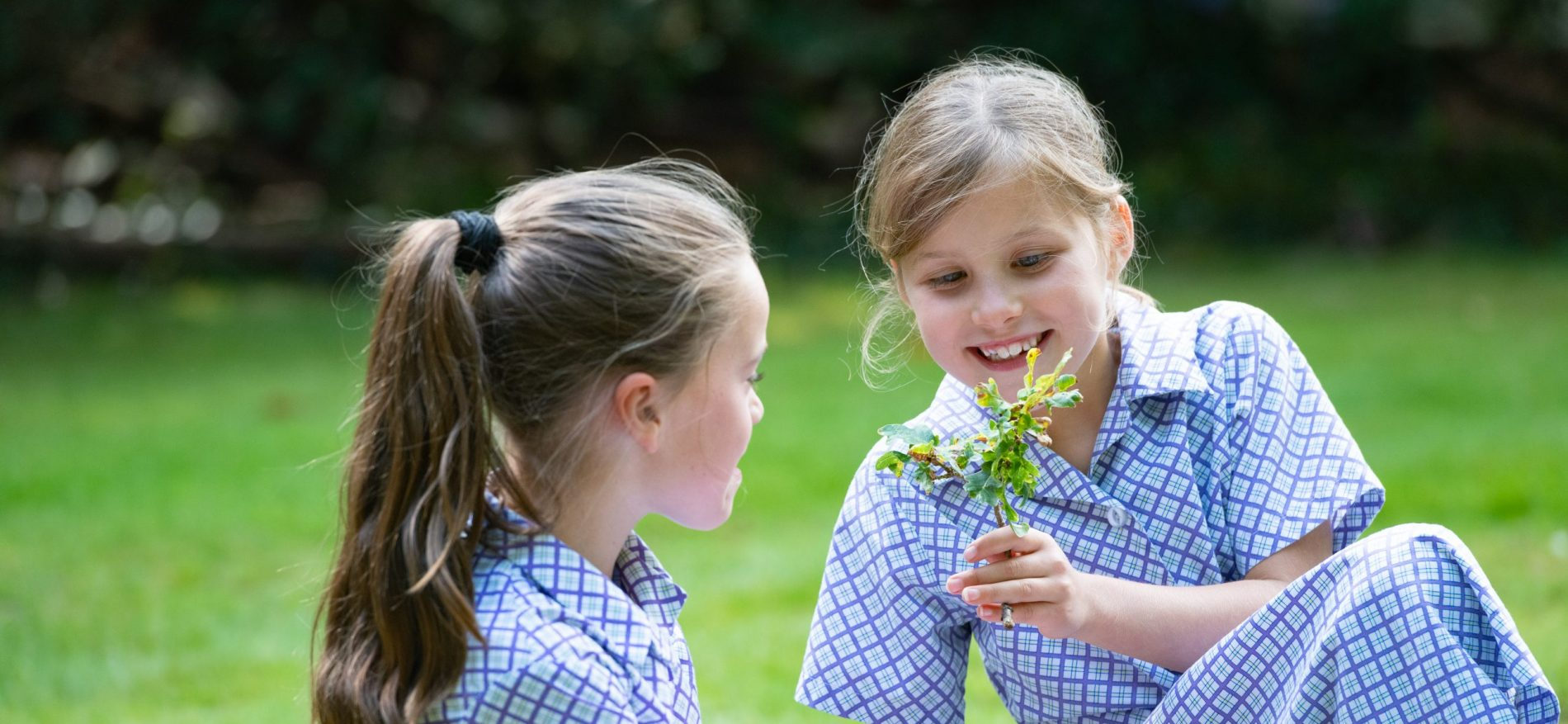 A girl shows another girl a flower they found