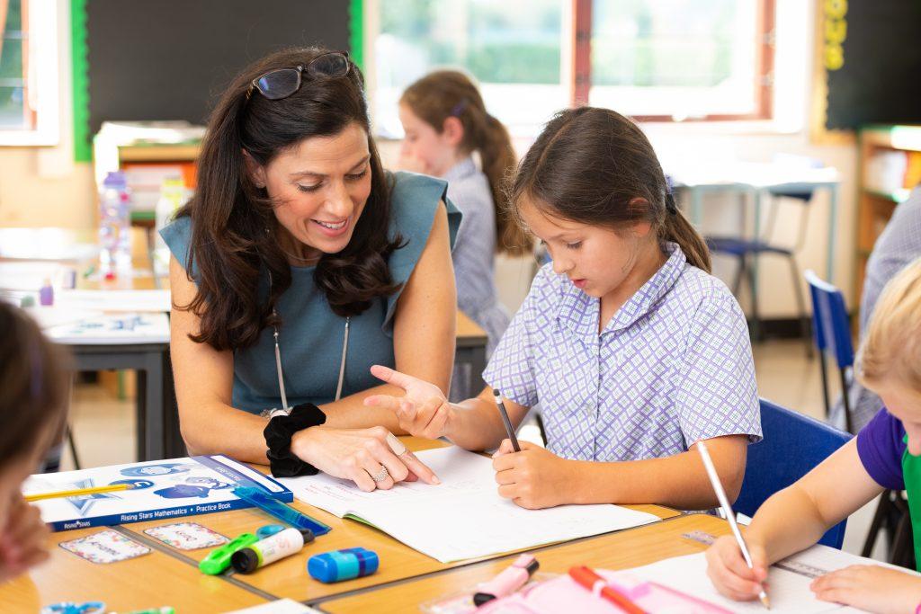 A teacher helping a student with their Maths work