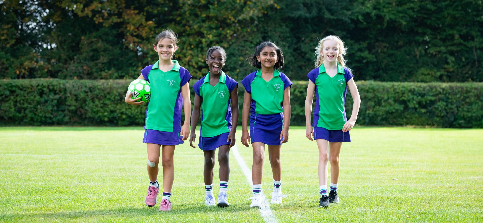 4 students with one holding a football walking along the pitch